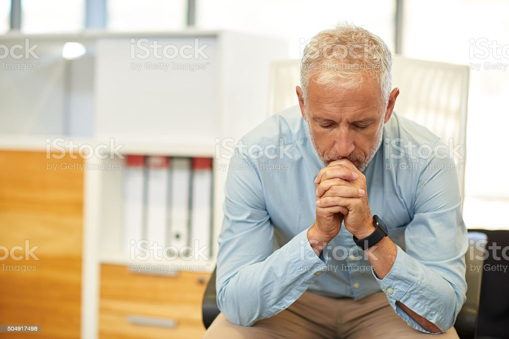 Businessman looking tired in real office location stock photo