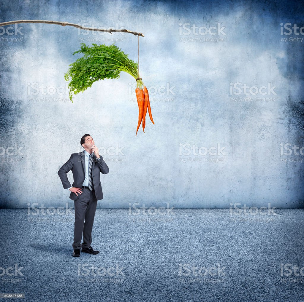 Businessman Looking Up At A Carrot Dangling From A Stick stock photo