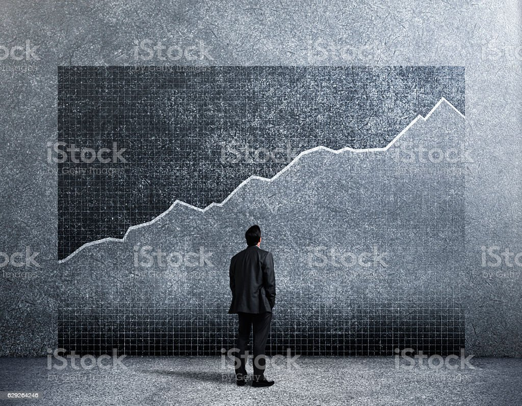 Businessman Looking Up At Growth Chart On Wall stock photo