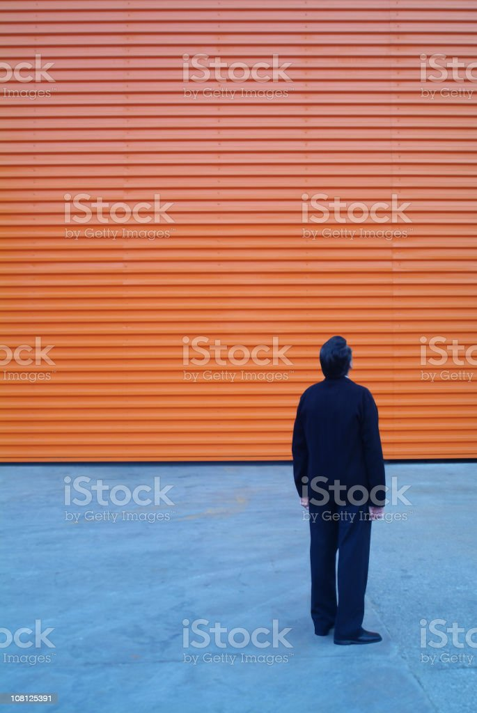 Businessman Looking Up at Orange Building Facade royalty-free stock photo