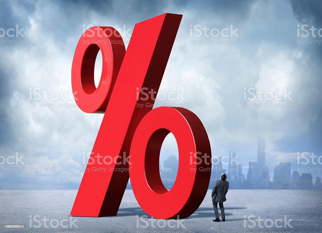 Businessman Looking Up At Percent Sign stock photo