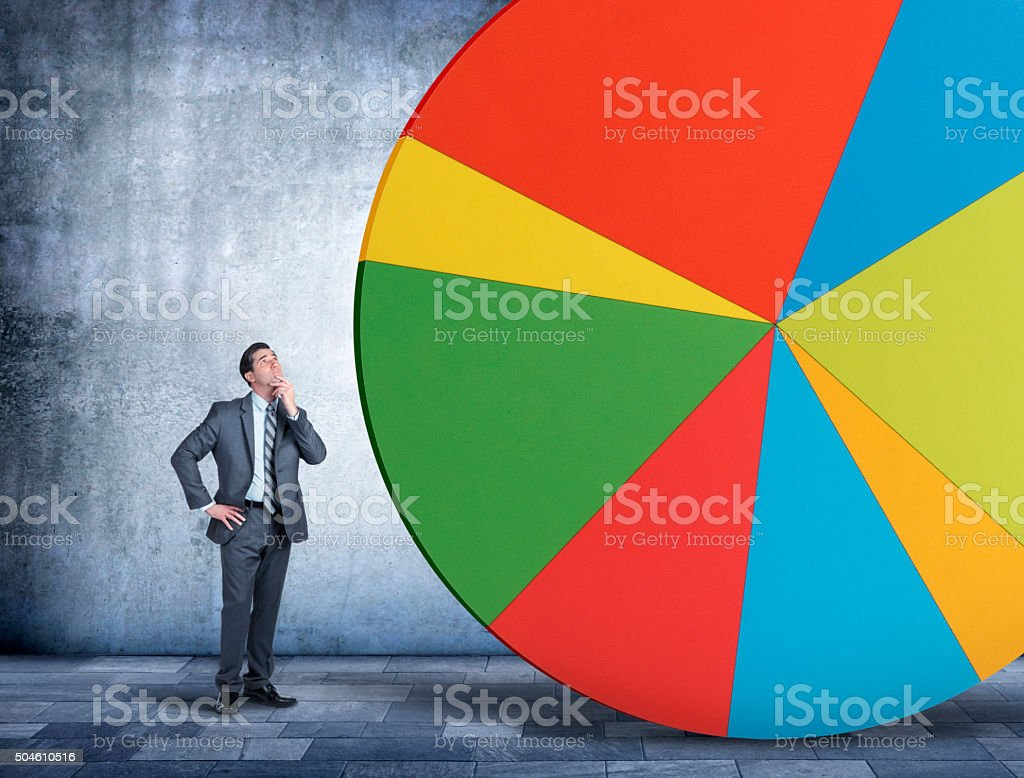Businessman Looking Up At Pie Chart stock photo