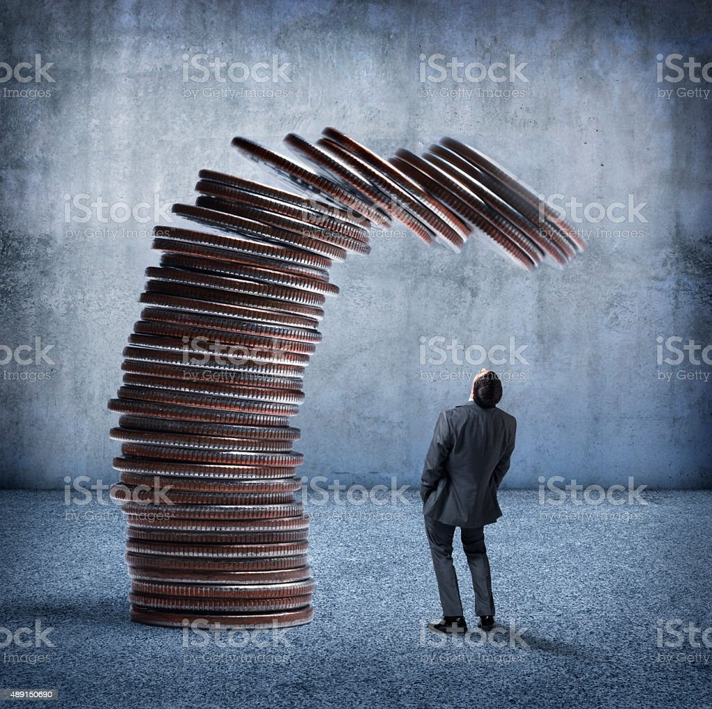 Businessman looking Up At Stack Of Coins Ready to Fall stock photo