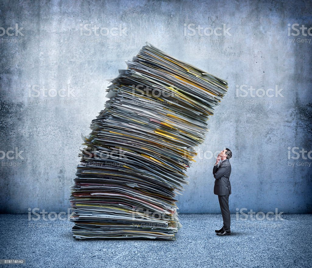 Businessman Looking Up At Stack Of Falling Paperwork stock photo