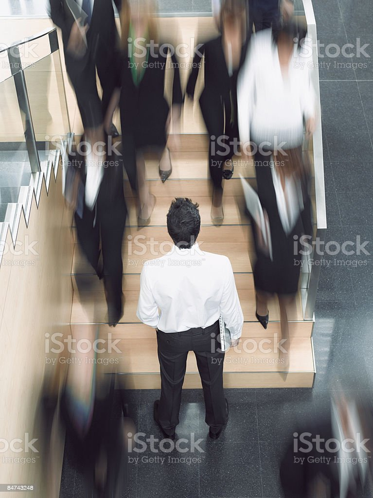 Businessman looking up busy office staircase stock photo