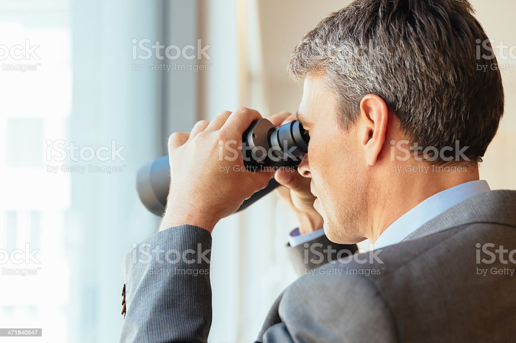 Businessman Looking with Binoculars Through the Window royalty-free stock photo