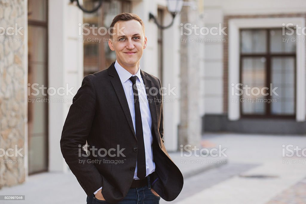 Businessman looks and smiles stock photo