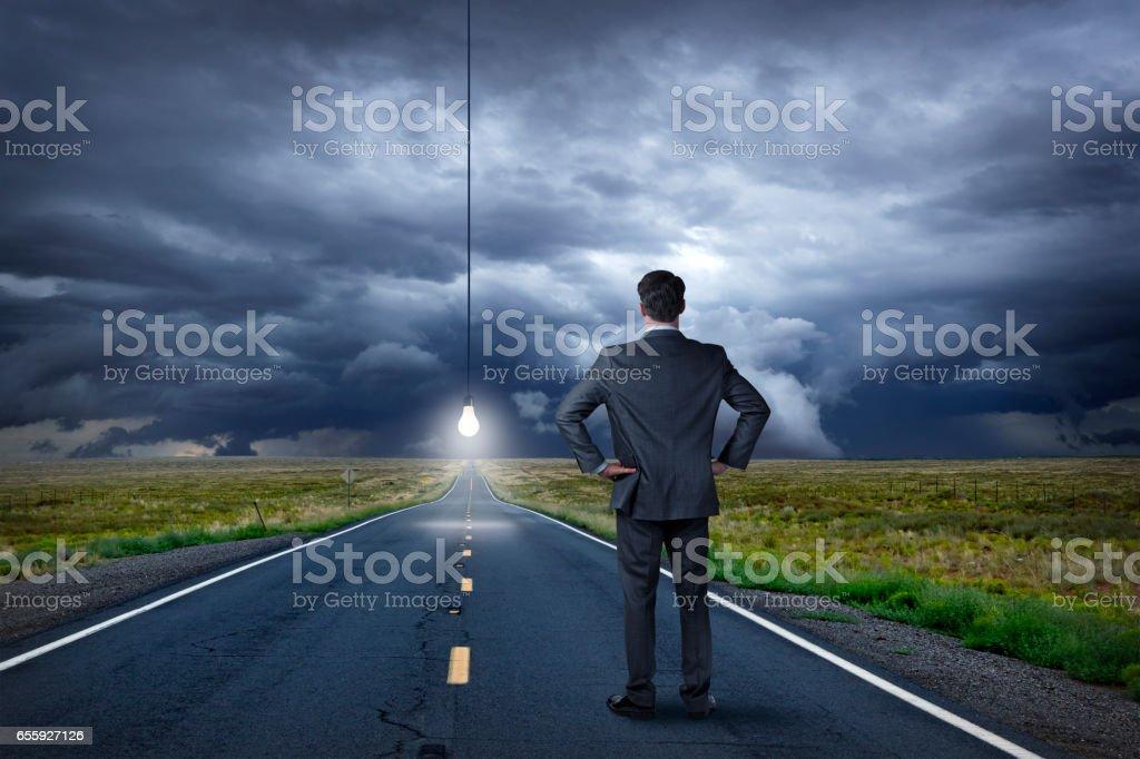 Businessman Looks At Lightbulb Illuminating Long Straight Rural Road stock photo