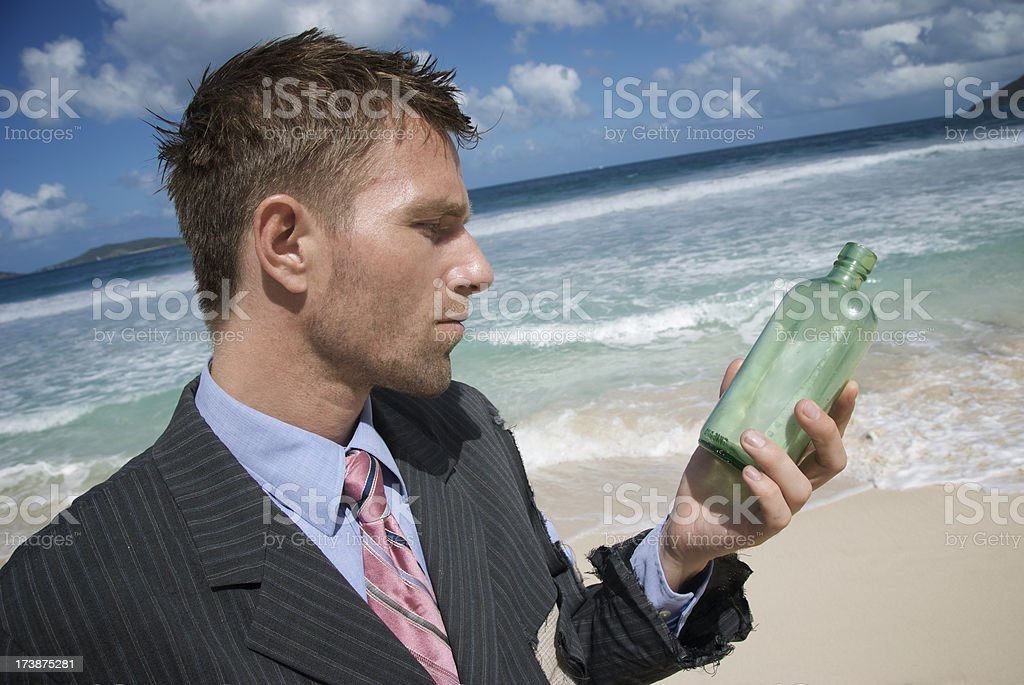 Businessman Looks at Message in a Bottle royalty-free stock photo