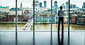 Businessman looks at the London Skyline from his Office Window