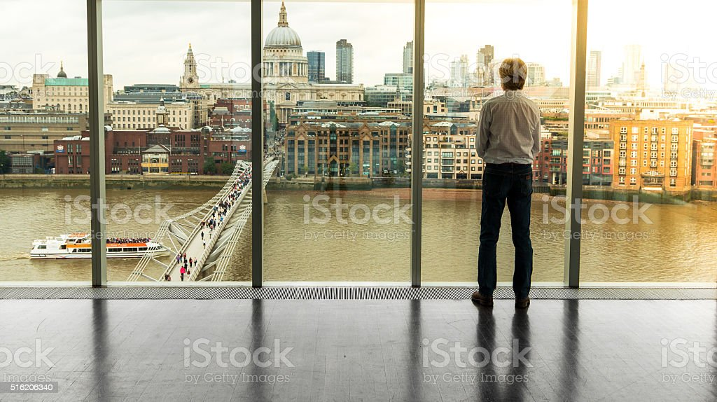 Businessman looks at the London Skyline from his Office Window stock photo