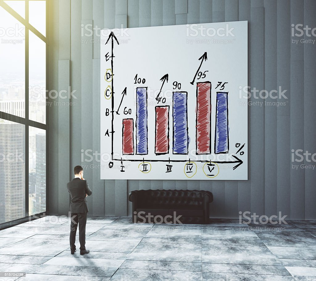 Businessman looks at the poster with business graph in modern stock photo