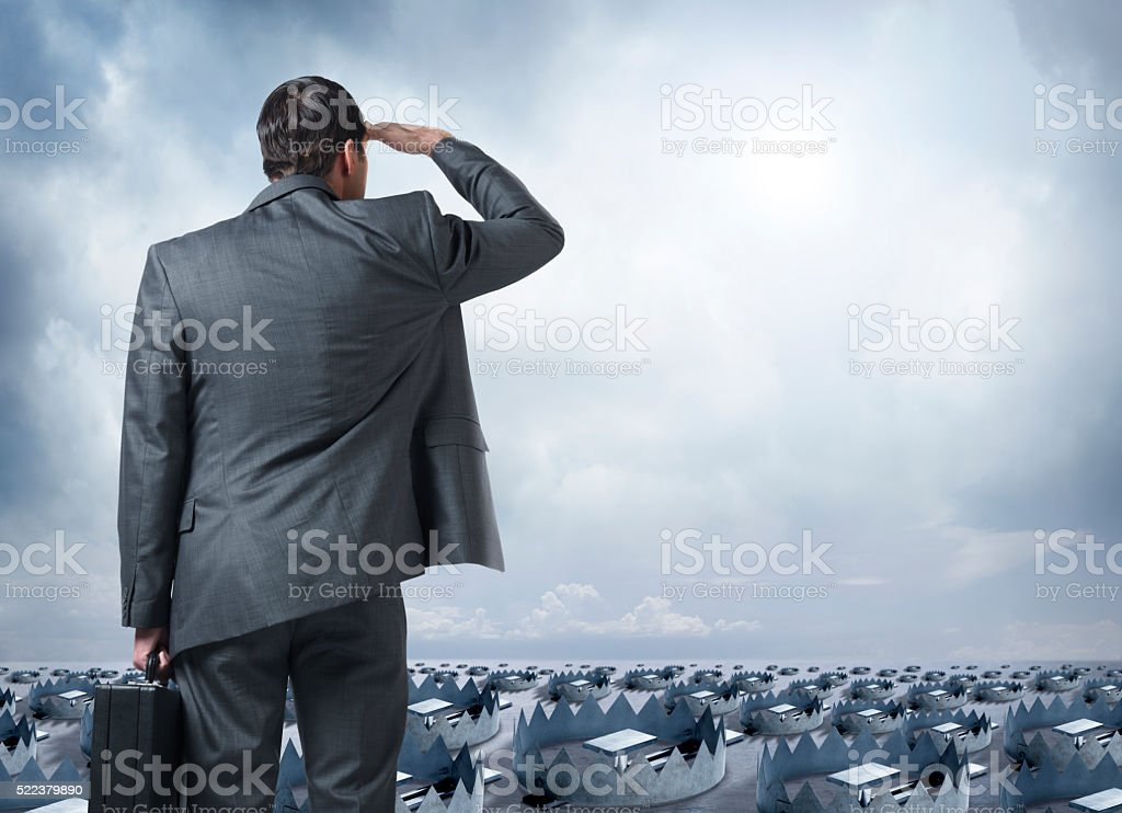 Businessman Looks Out Into The Distance Littered With Traps stock photo