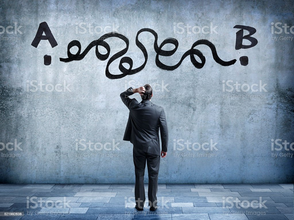 Businessman Looks Up At Complicated Solution To Easy Problem stock photo