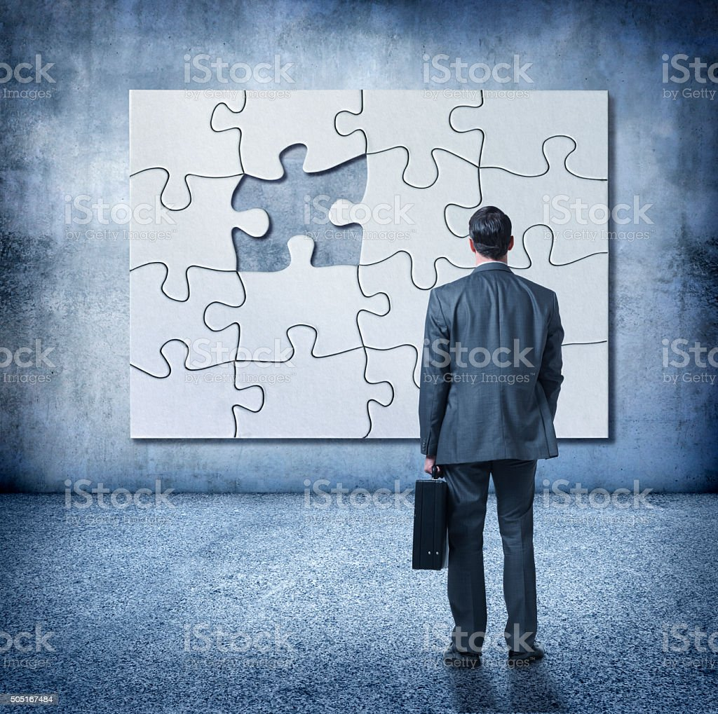 Businessman Looks Up At Puzzle With missing Piece stock photo
