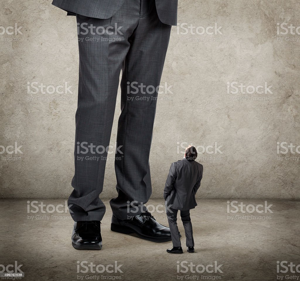 Businessman Looks Up Towards Much Larger Businessman stock photo
