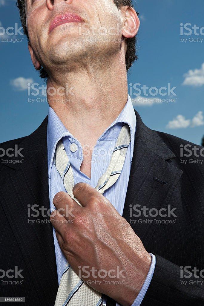 Businessman loosening his tie outdoors stock photo