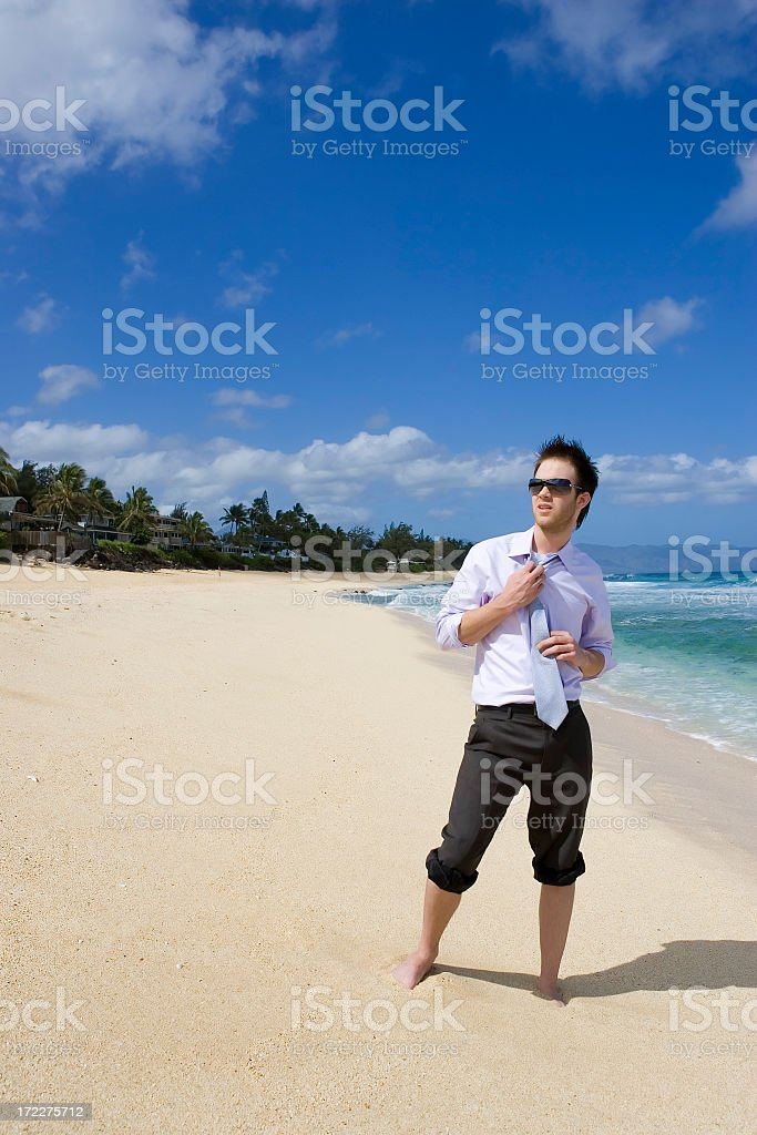 Businessman Loosening Tie on Beach royalty-free stock photo