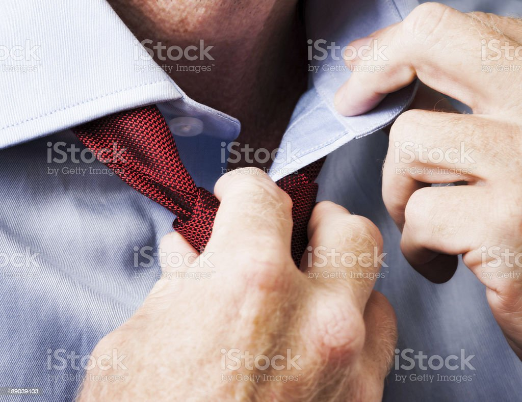 Businessman loosening tie stock photo