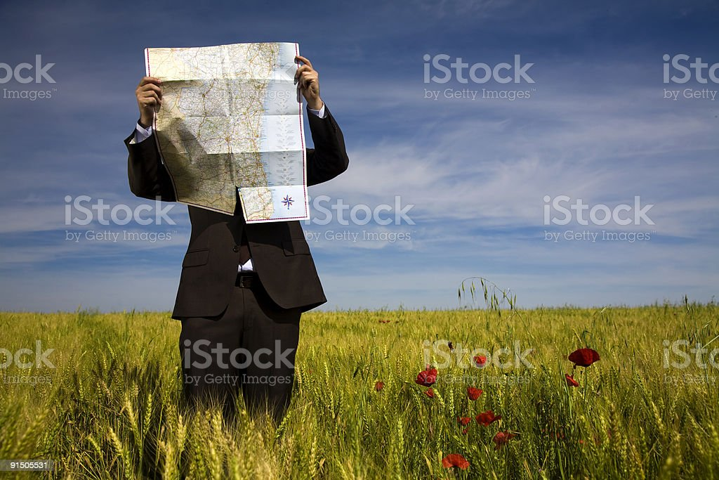 businessman lost in field using map stock photo
