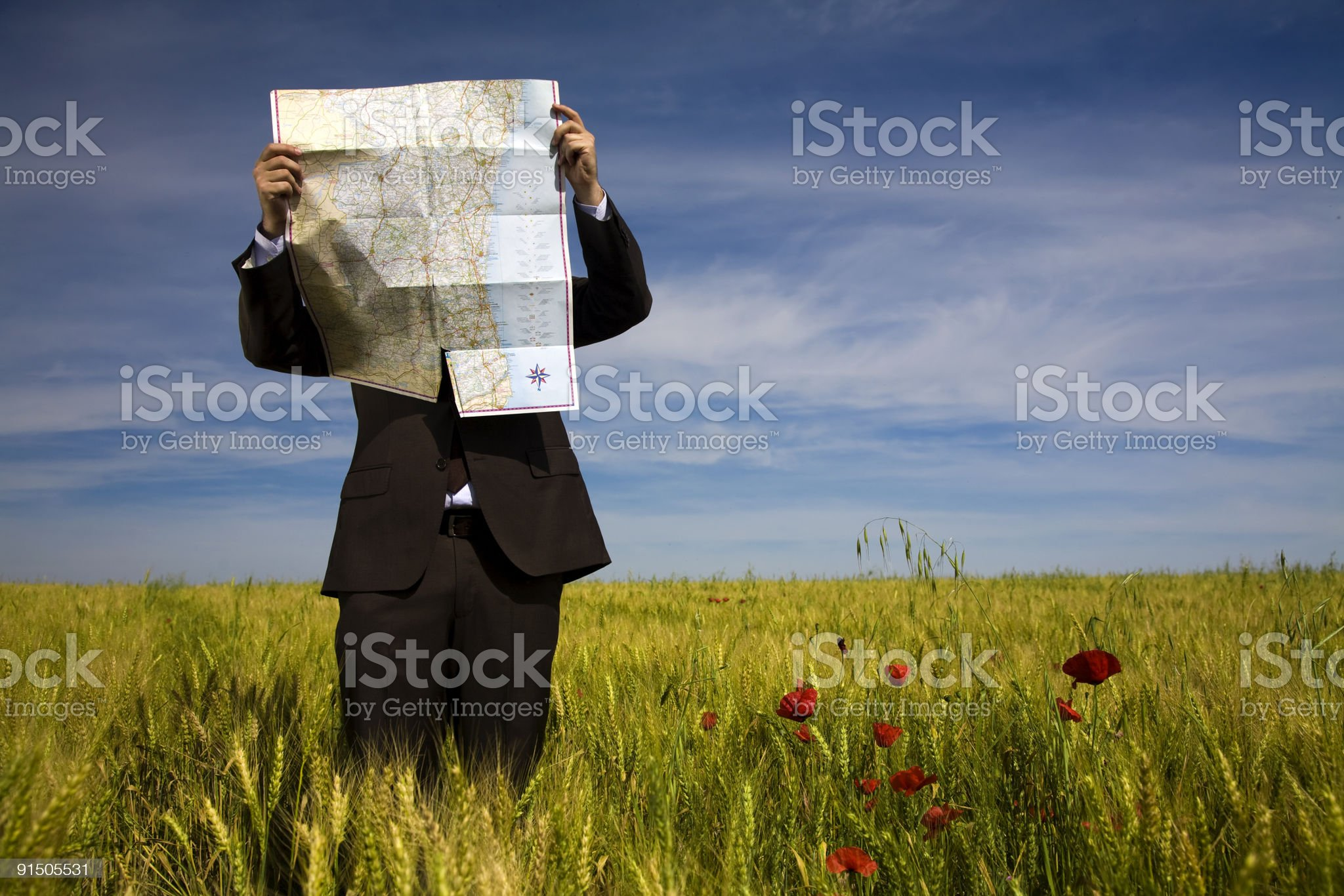 businessman lost in field using map royalty-free stock photo