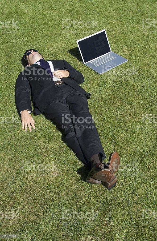 Businessman lying down on grass, Istanbul, Turkey royalty-free stock photo