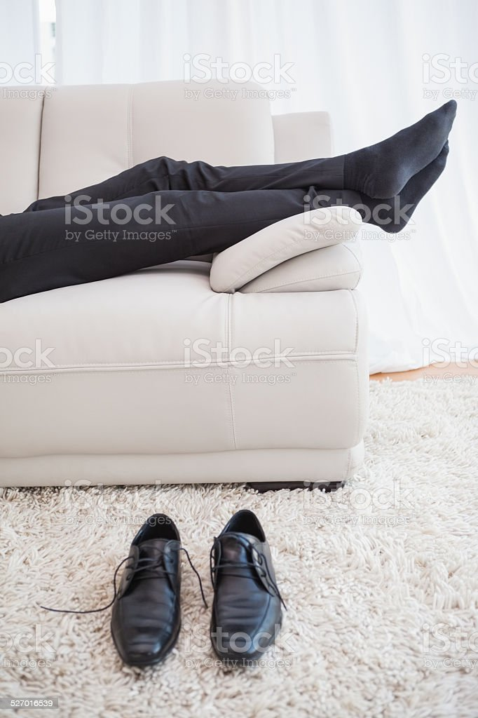 Businessman lying on couch legs only visible stock photo