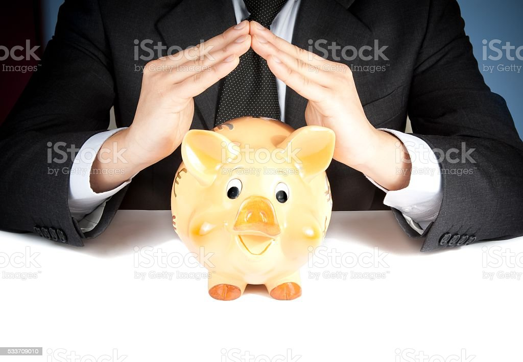 businessman make with hand a home behind a piggy bank stock photo