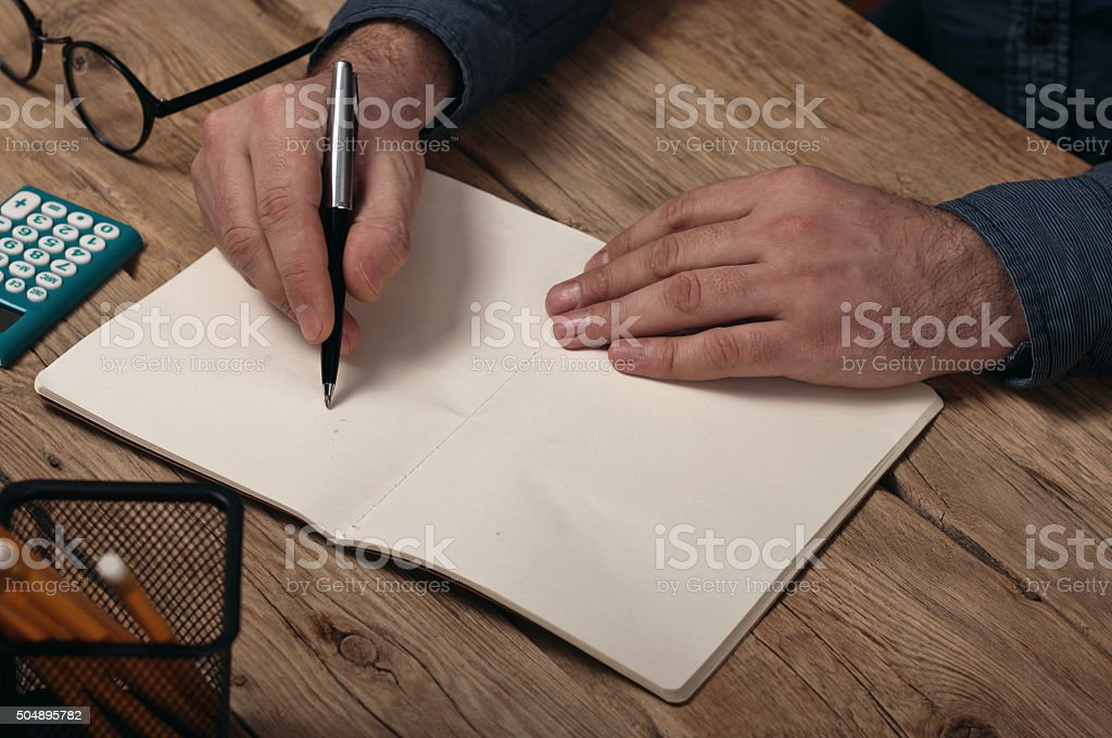 Businessman makes a note at notebook stock photo