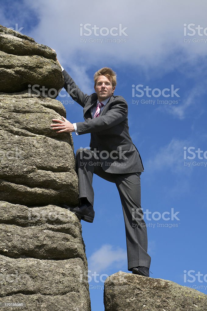 Businessman Makes Final Ascent Up Rock Face royalty-free stock photo