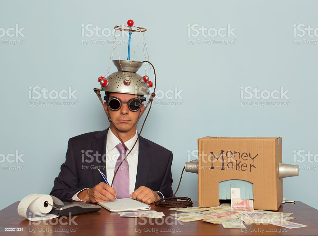 Businessman Makes Money with Helmet and Money Machine stock photo