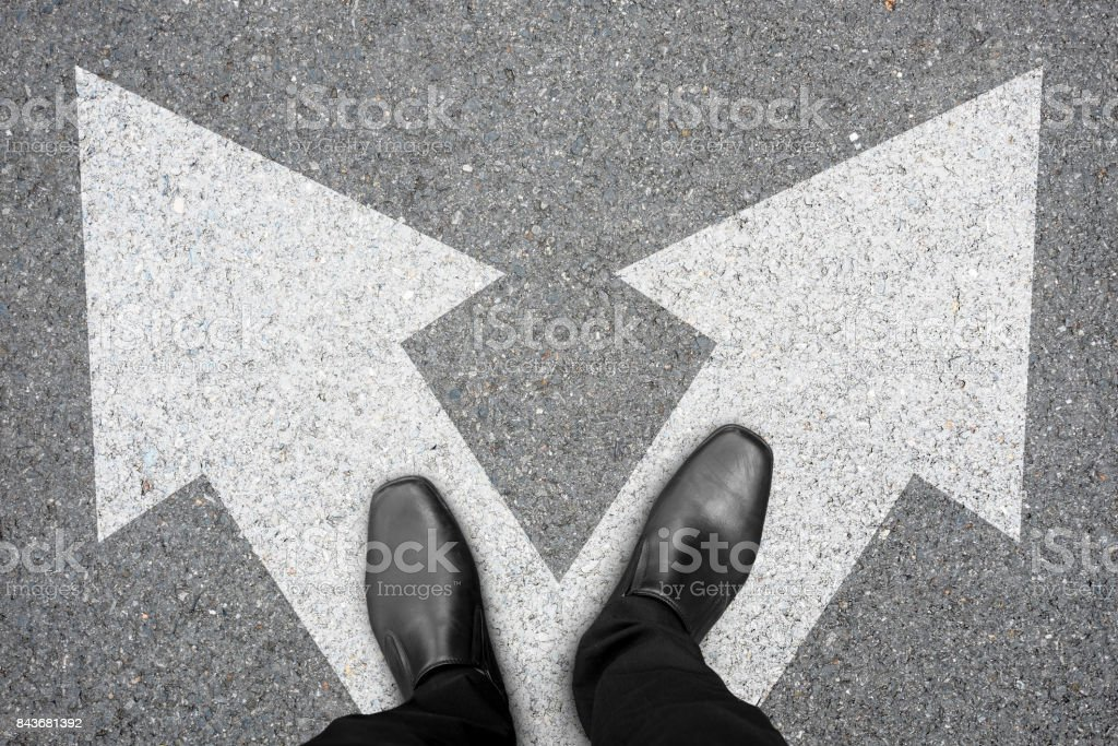 Businessman in black shoes standing at the crossroad making decision...