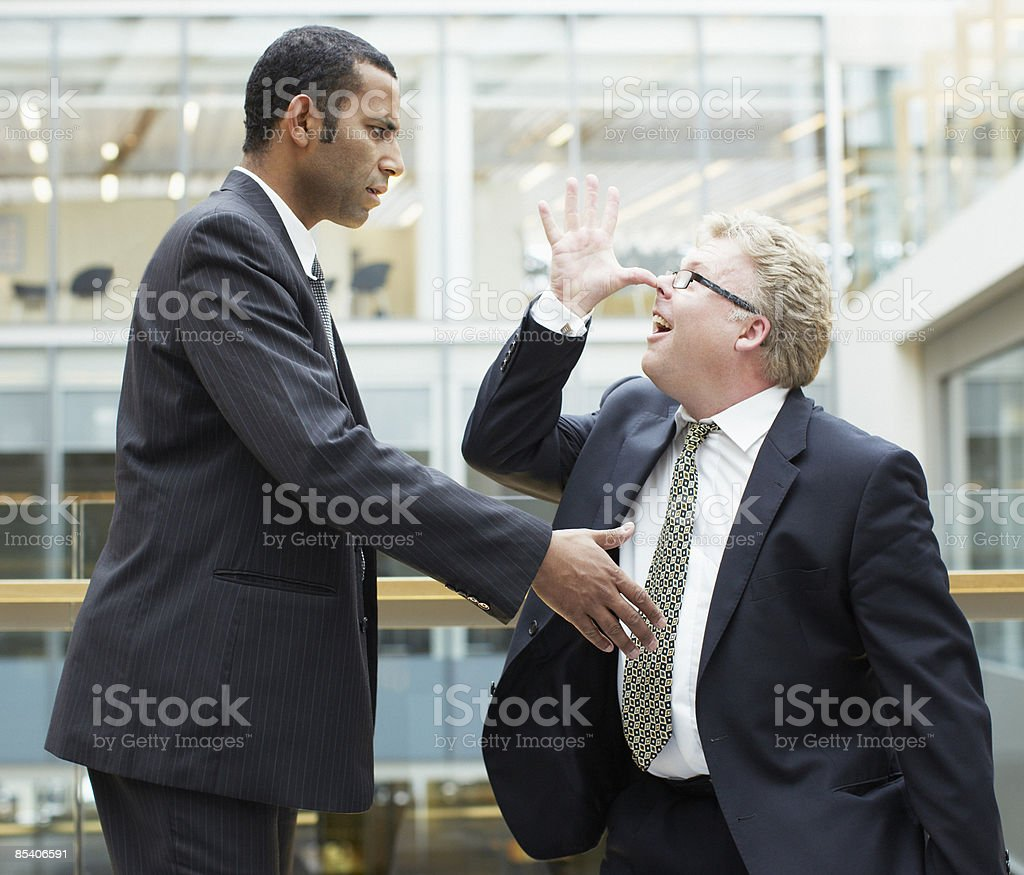 Businessman making face at co-worker stock photo