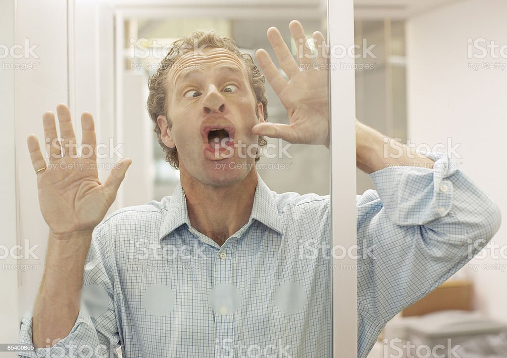 Businessman making face on glass wall royalty-free stock photo