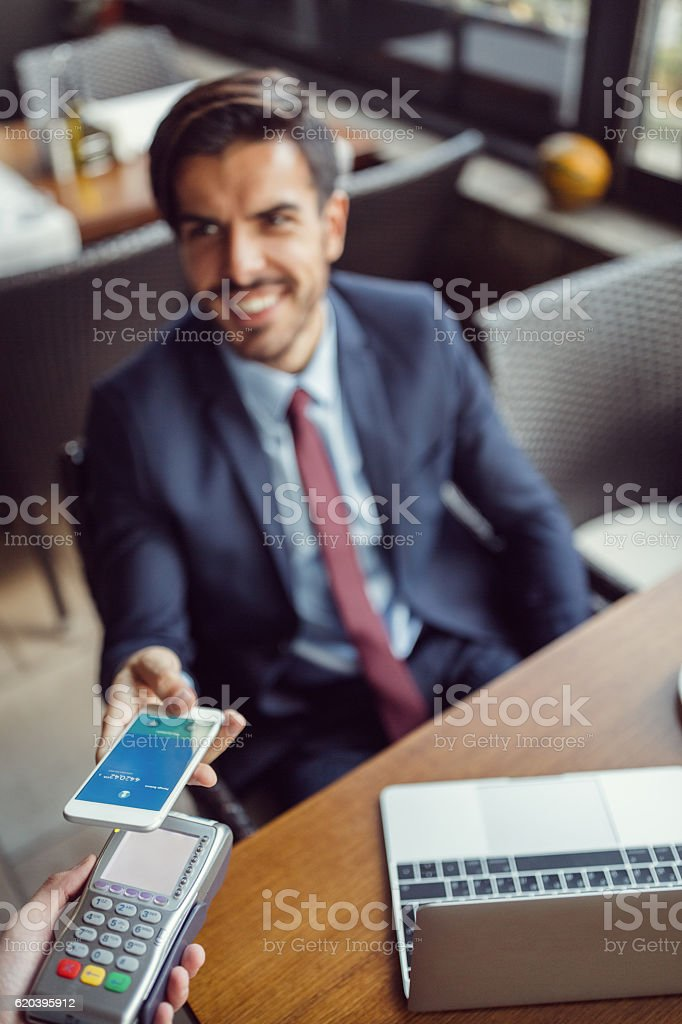 Businessman making mobile payment stock photo