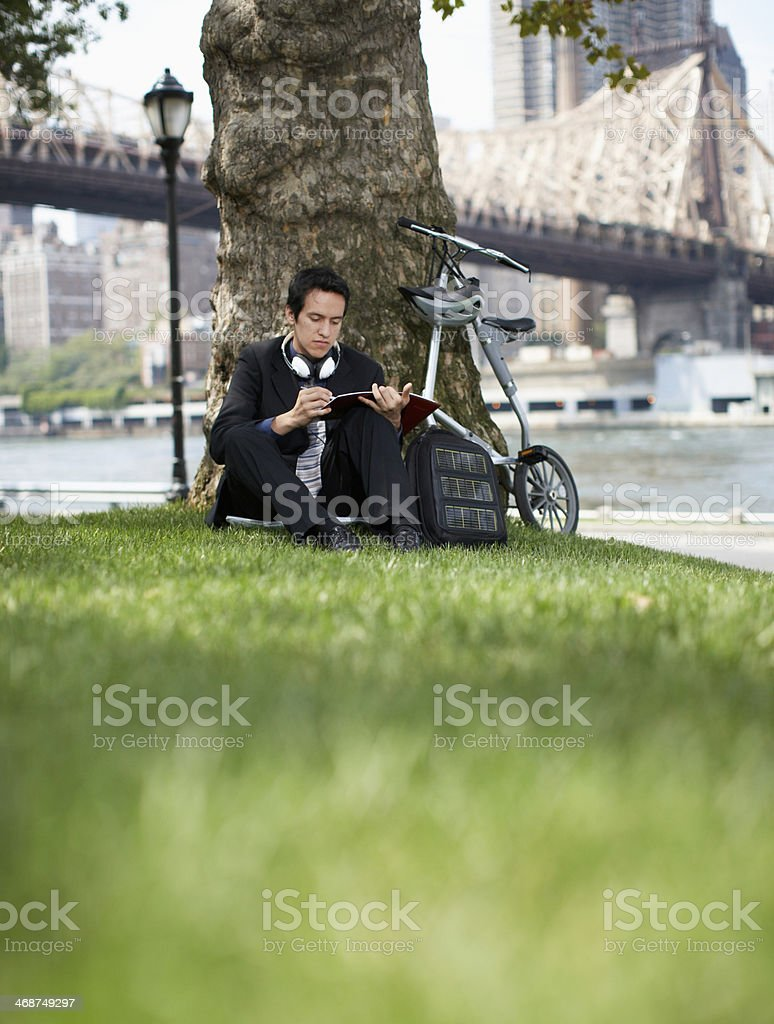 Businessman Making Notes Under Tree stock photo