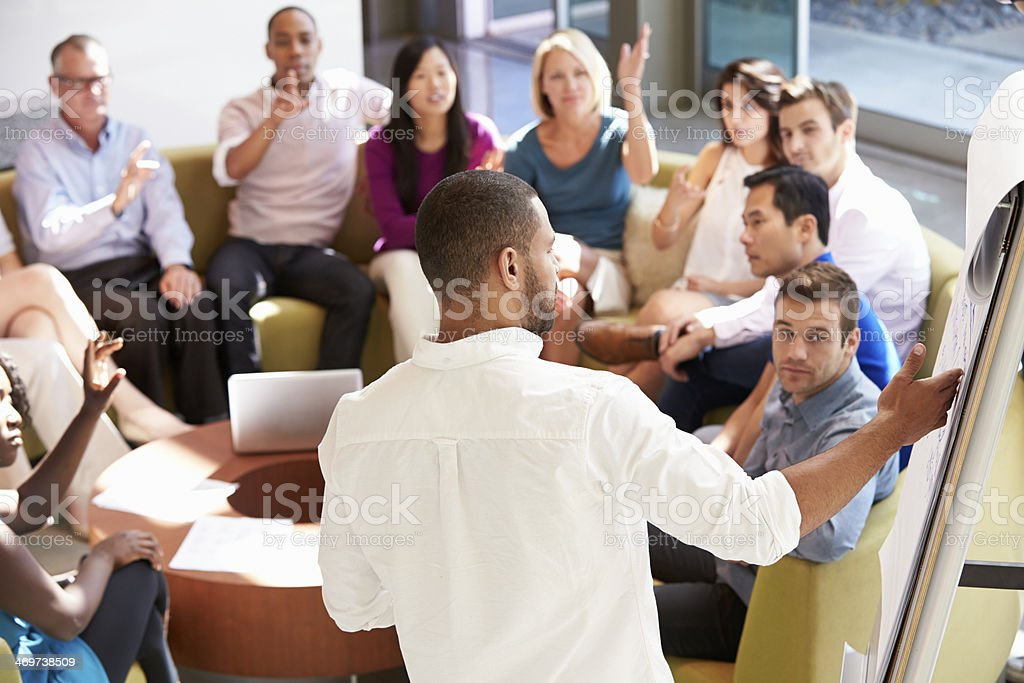 Businessman Making Presentation To Office Colleagues stock photo