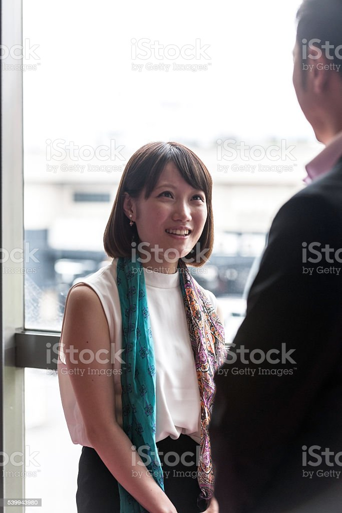 Businessman man, woman, talking in a business lobby,Kyoto,Japan stock photo