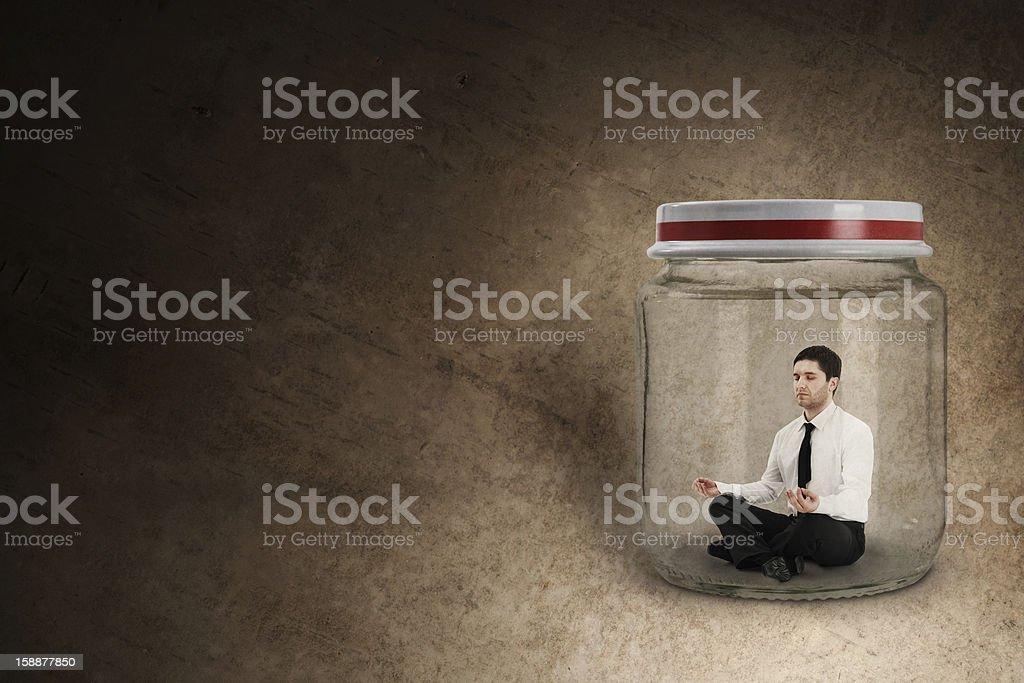 Businessman meditating in jar stock photo