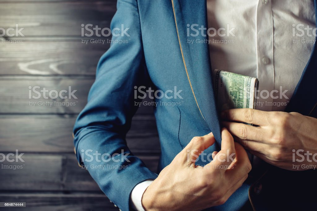 Businessman, member or officer puts a bribe in his pocket stock photo