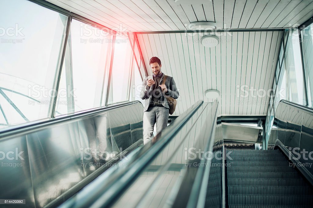 Businessman moving down escalator stock photo