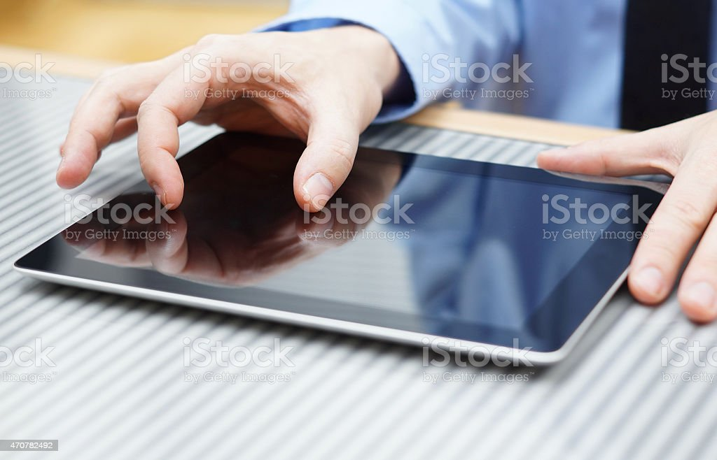 businessman moving two  fingers on touchscreen on  tablet computer stock photo