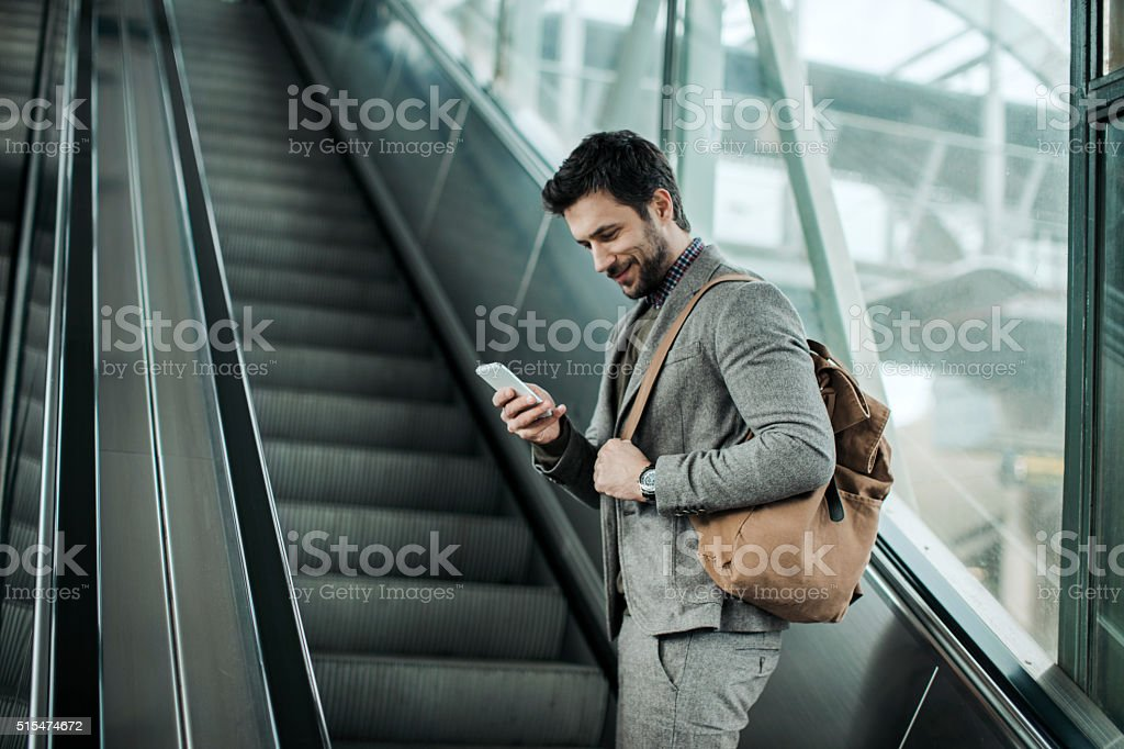 Businessman moving up escalator stock photo