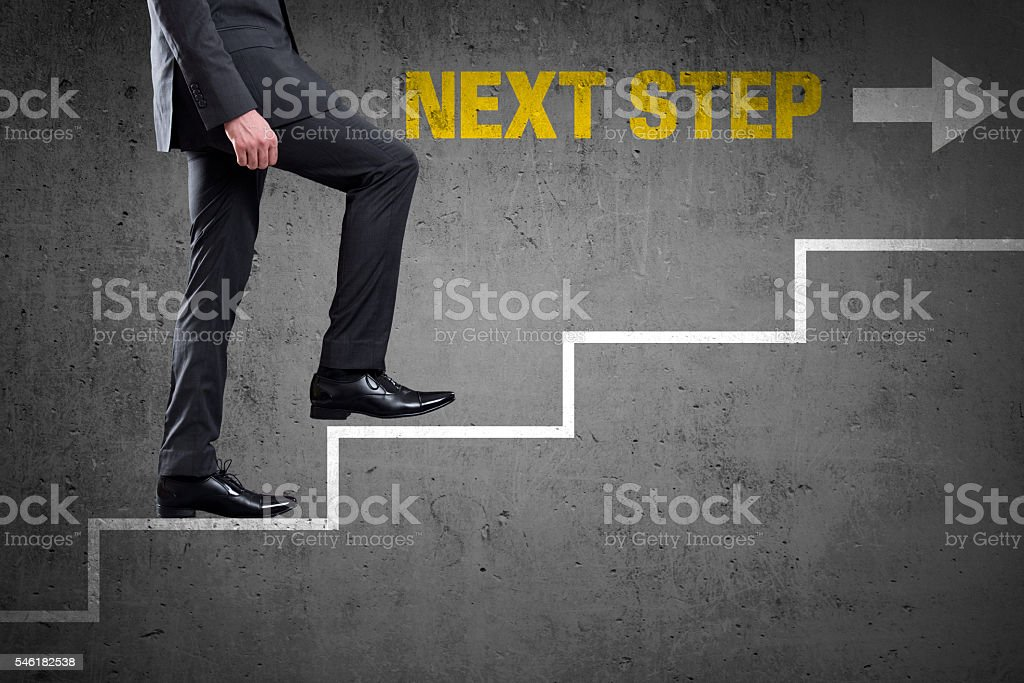 Low section view of a businessman climbing on stairs representing the...