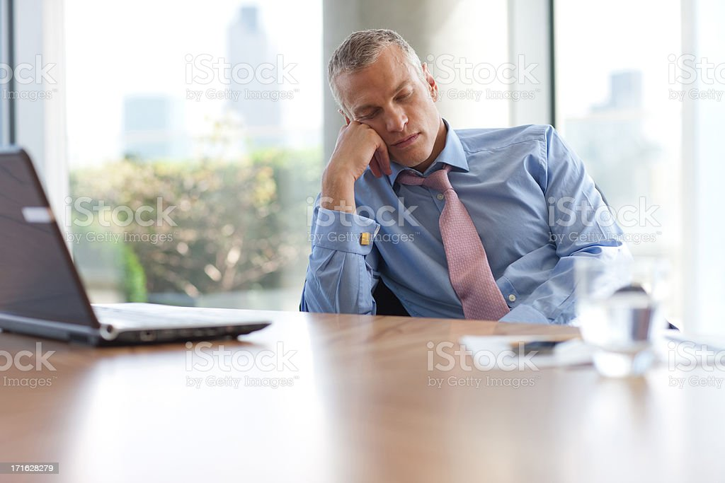 Businessman napping at desk in office stock photo