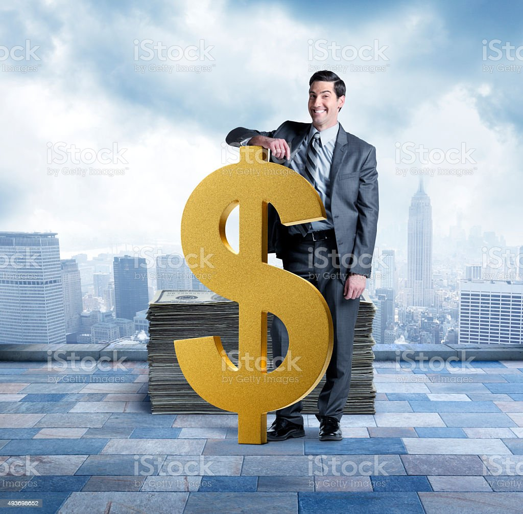 Businessman Next To Large Dollar Sign With Stack Of Money stock photo