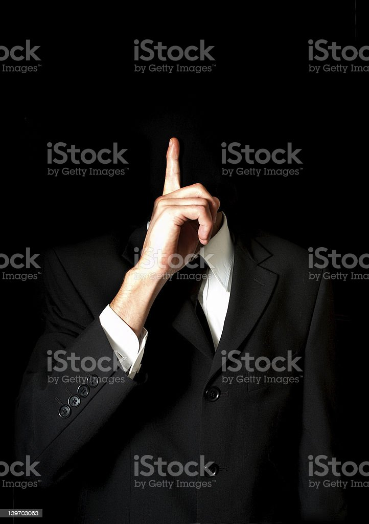 A businessman not showing his face motioning to be quiet stock photo