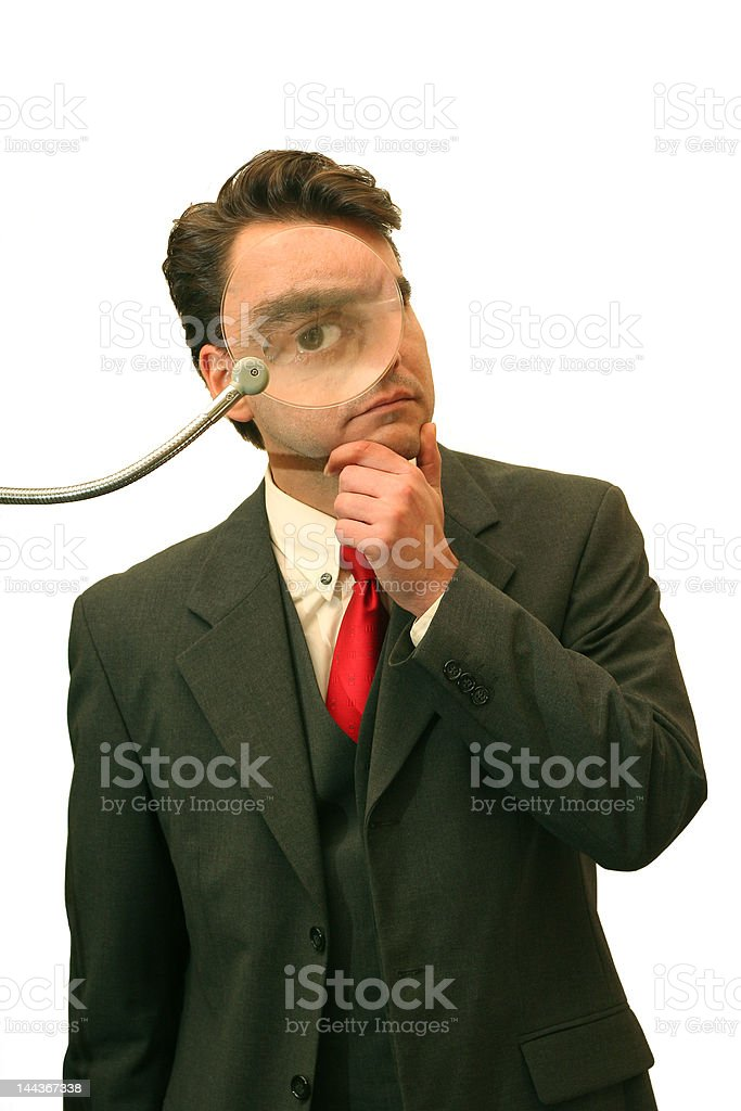 Businessman observing through magnifier royalty-free stock photo