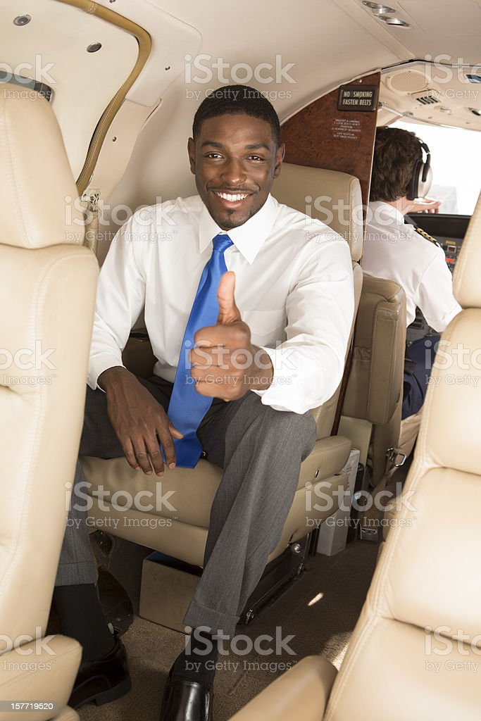 Businessman offering a thumbs up inside of Corporate Jet royalty-free stock photo