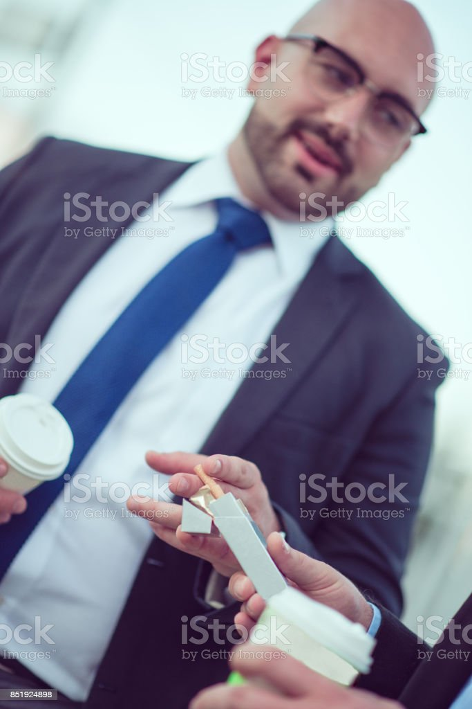 Businessman Offering Cigaret to A Colleague and Drinking Coffee After Work stock photo